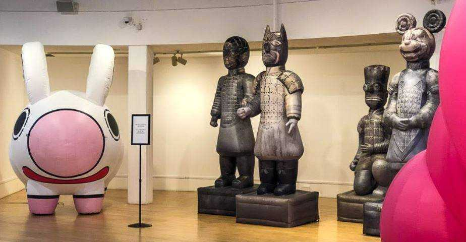 Various inflatable sculptures in a gallery - including a large animated rabbit and grey statues with contemporary heads on classic Chinese-inspired armor.
